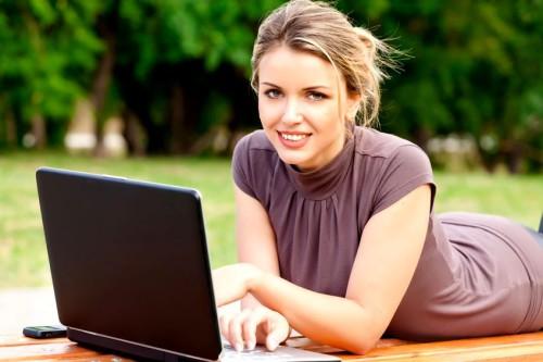 Красивая девушка ищет варианты заработка денег в интернете с помощью ноутбука