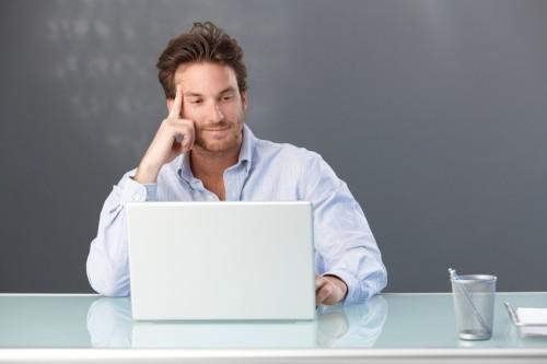 Мужчина думает сидя за столом напротив ноутбука