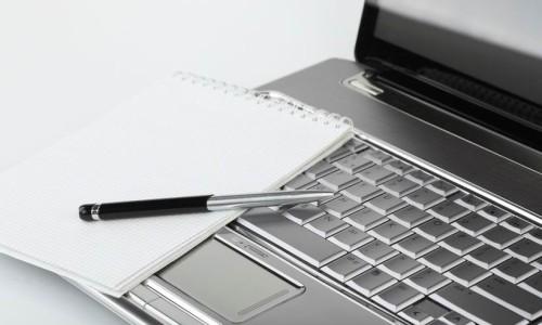 Ноутбук копирайтера, блокнот и ручка