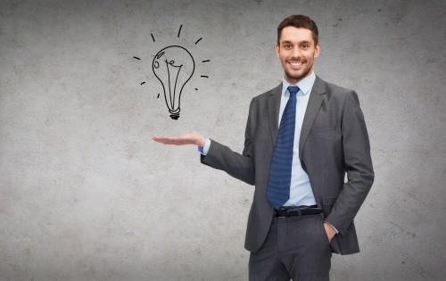 Парень в костюме держит на руке виртуальную лампочку-идею