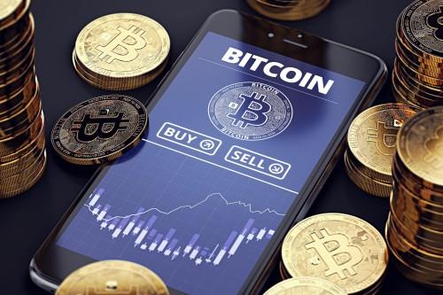 Смартфон и монеты Биткоин
