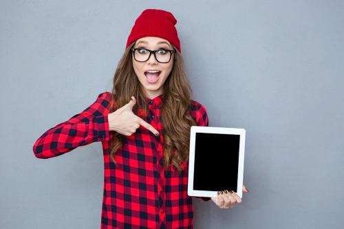 Девушка показывает на планшет с помощью которого она создала инфобизнес
