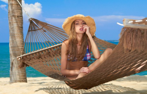 Красивая девушка лежит в гамаке на берегу моря