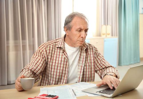 Пенсионер мужчина ищет с помощью ноутбука хорошие идеи для малого бизнеса