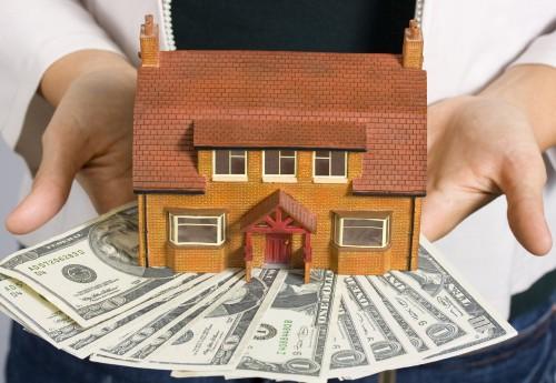 Частный дом и доллары в руках мужчины