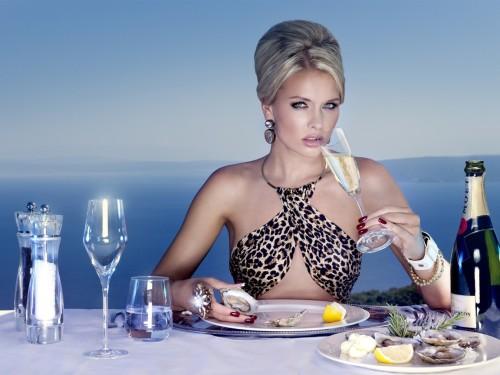 Счастливая и богатая девушка ужинает в дорогом ресторане