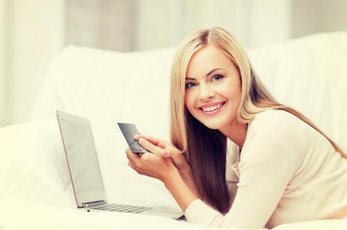 Красивая девушка, ноутбук и кредитная карта