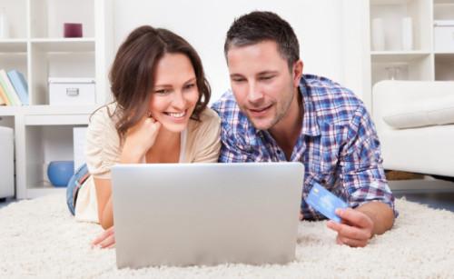 Муж и жена лежат на диване за ноутбуком и ищут способы, как взять кредит