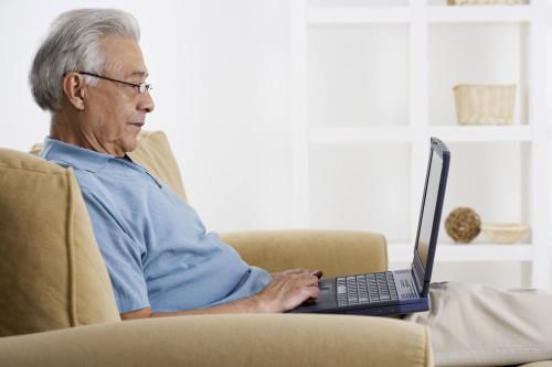 Пенсионер сидит на диване за ноутбуком