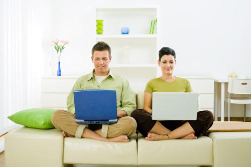 Муж и жена сидят на диване с ноутбуками в руках