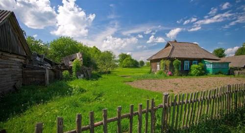 Деревенский дом, сарай, забор и вспаханное поле