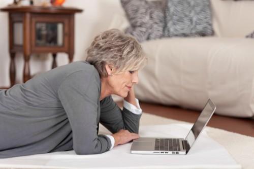 Женщина пенсионер лежит на полу напротив ноутбука и ищет работу через Интернет