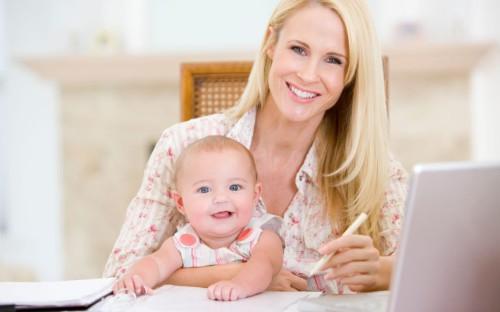 Мама сидит с ребёнком на  стуле за ноутбуком