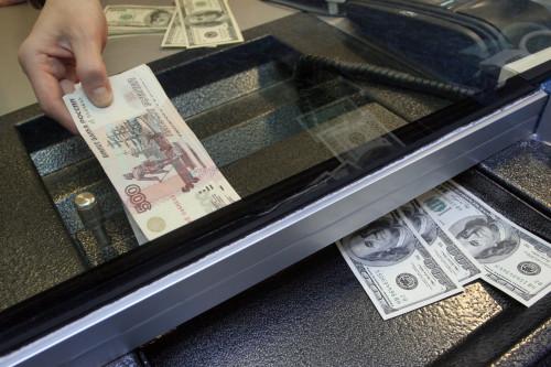 Человек покупает доллары за рубли в обменном пункте