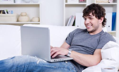 Парень сидит на диване за ноутбуком