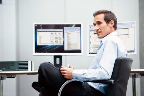 Программист сидит в кресле напротив мониторов от компьютера