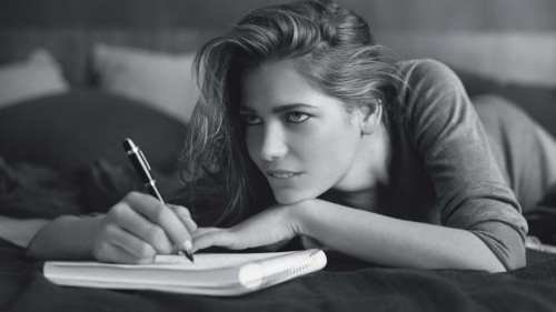 Красивая девушка пишет резюме на работу