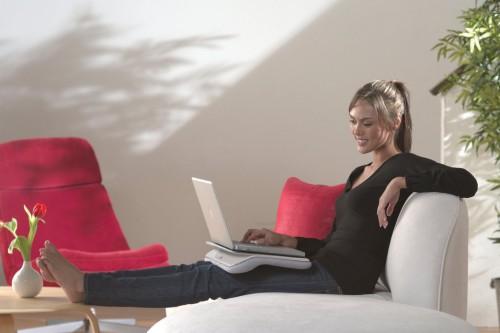 Девушка сидит на диване и в руках держит ноутбук