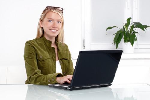Симпатичная девушка сидит за ноутбуком