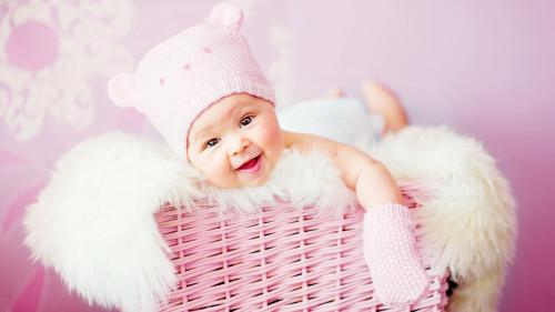 Красивый малыш в корзине в фирменной одежде из интернет-магазина