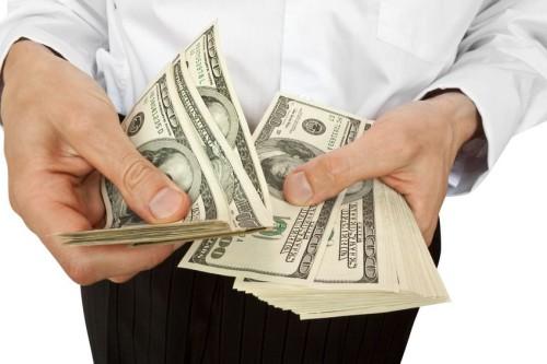 Мужчина держит в руке много долларов