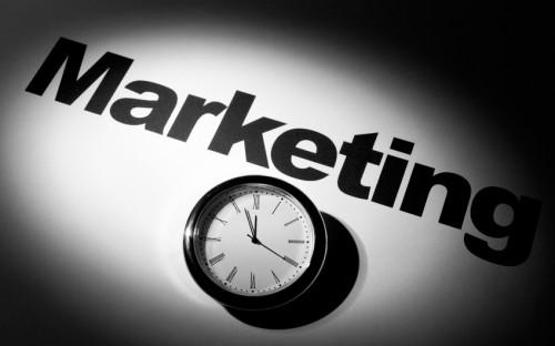 Надпись маркетинг и часы показывающие время
