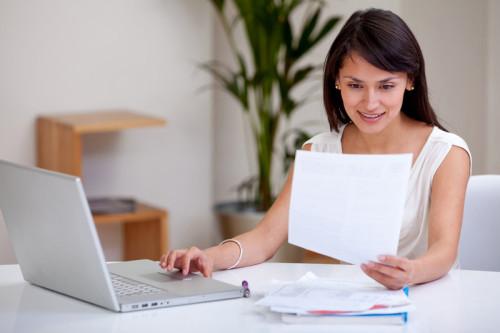 Красивая девушка сидит за столом напротив ноутбука, и держит в руках лист бумаги