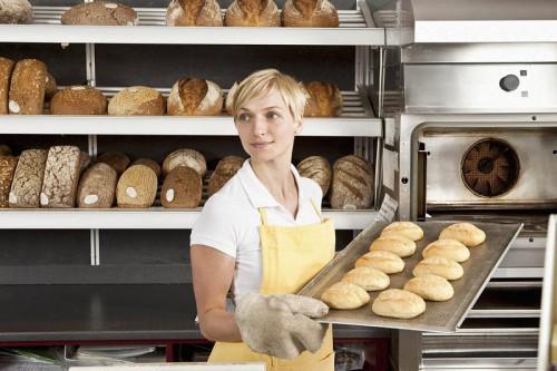Девушка в цеху пекарни держит на подносе свежеиспечённый хлеб