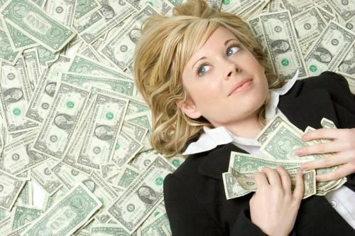 Красивая девушка лежит на полу осыпанная долларами и думает о том, как заработать денег сидя дома