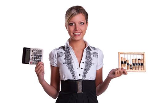 Девушка держит в руках калькулятор и счёты