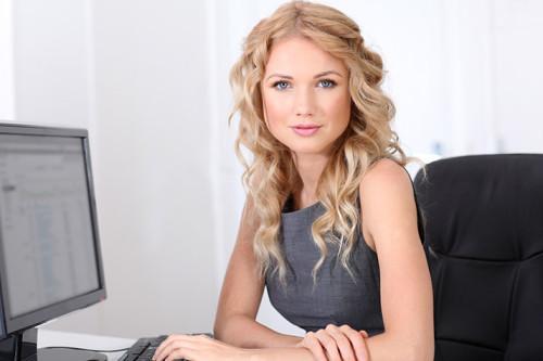 Красивая девушка блондинка работает за компьютером