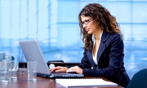 Девушка в очках сидит за столом напротив ноутбука и ищет информацию в интернете