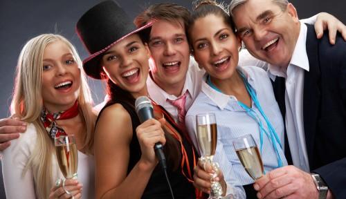 Девушки и парни на празднике с бокалами шампанского в руках