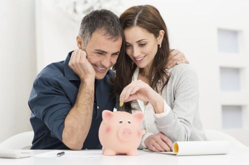 Муж и жена складывают сэкономленные деньги в копилку