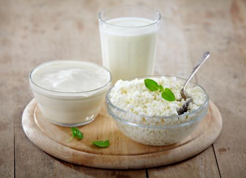 Творог, сметана и молоко в посуде на столе