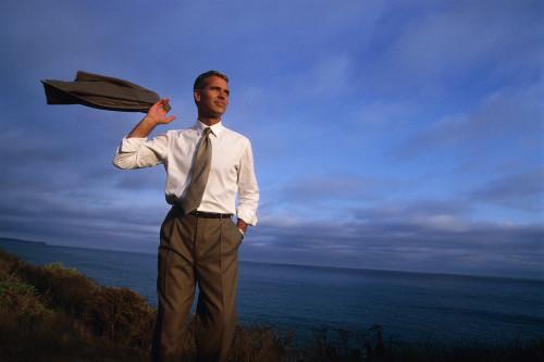 Уверенный мужчина альфа самец стоит на скале на берегу моря