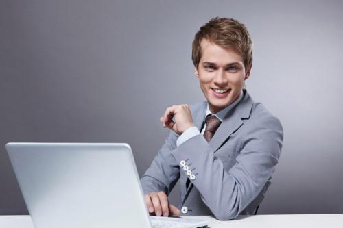 Красивый парень в костюме сидит напротив ноутбука