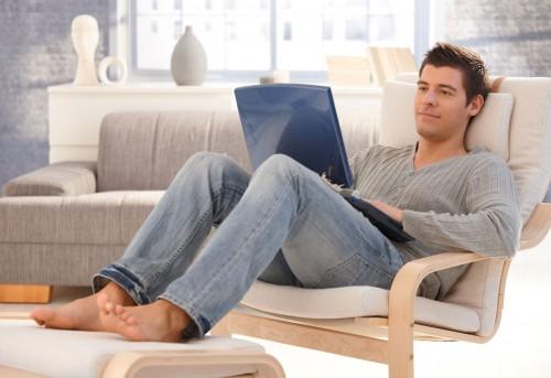 Парень сидит на диване с ноутбуком в руках