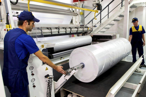 Рабочие в цеху производят полиэтиленовую плёнку
