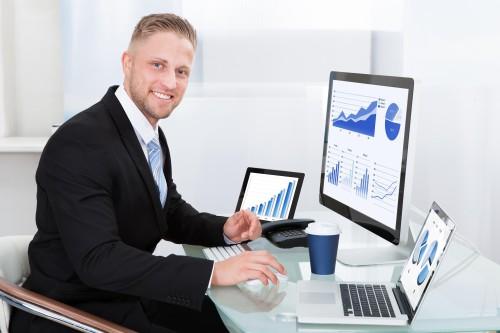Мужчина сидит напротив монитров и прогнозирует курс валют