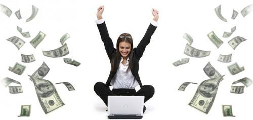 Девушка сидит напротив ноутбука в окружении долларов