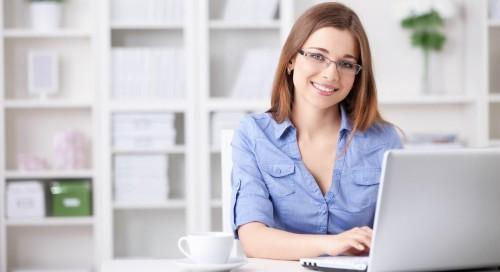 Красивая девушка в очках сидит за столом за ноутбуком