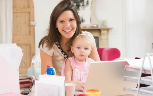 Молодая мама с ребёнком за ноутбуком