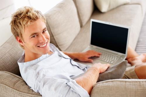 Красивый парень сидит на диване с ноутбуком в руках
