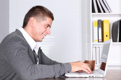 Парень сидит напротив ноутбука и зарабатывает деньги