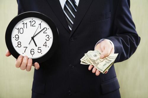 Парень в костюме держит в руках часы и деньги (доллары)