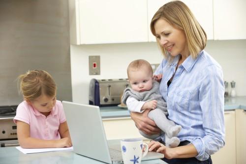 Мама с малышом на руках работает за ноутбуком
