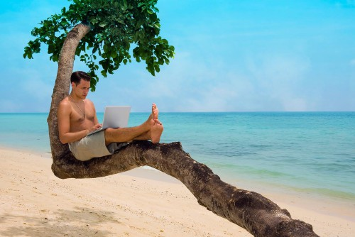 Парень с ноутбуком в руках сидит на дереве на тропическом острове и зарабатывает деньги через Интернет