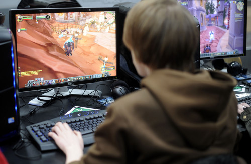 Молодой человек играет в игру на компьютере