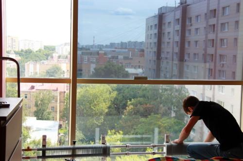 Мужчина тонирует окно в квартире
